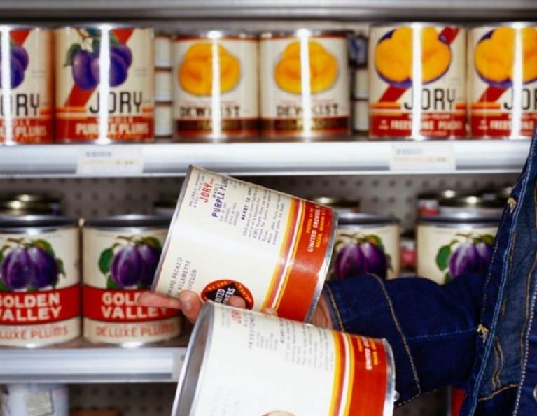 Cans on a grocery store shelf.