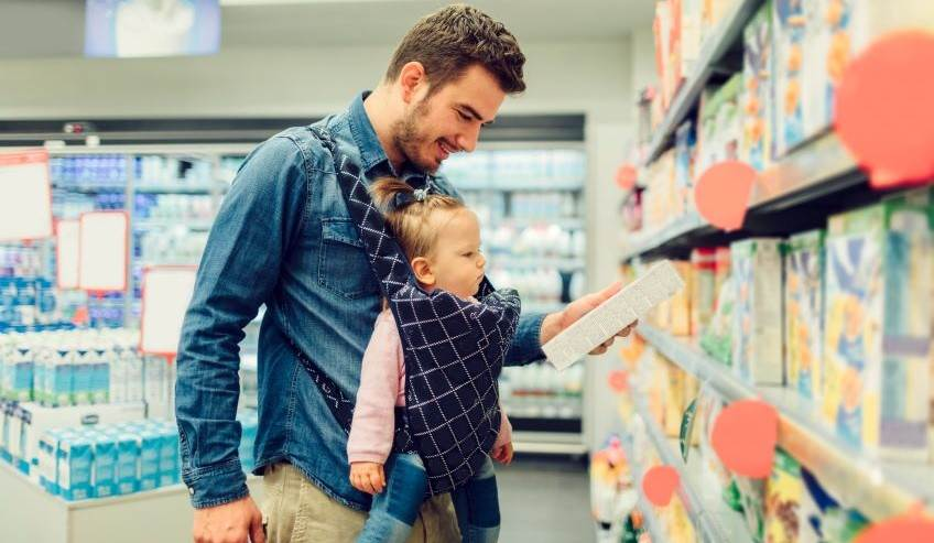 Dad and child looking at packaging in a retail store