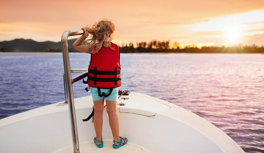 Little girl out on the front of a boat watching the sunset.